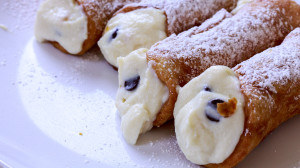 Crispy cannoli shells with a sweet ricotta filling studded with chocolate and candied citrus
